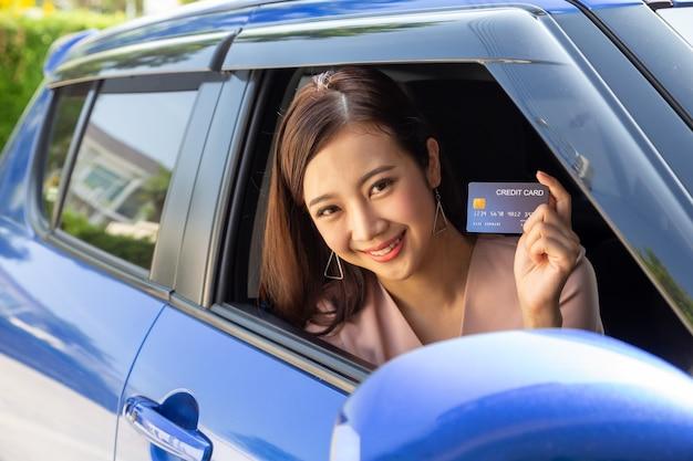 Jovem asiática feliz segurando um cartão de crédito