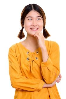 Jovem asiática feliz sorrindo enquanto pensa