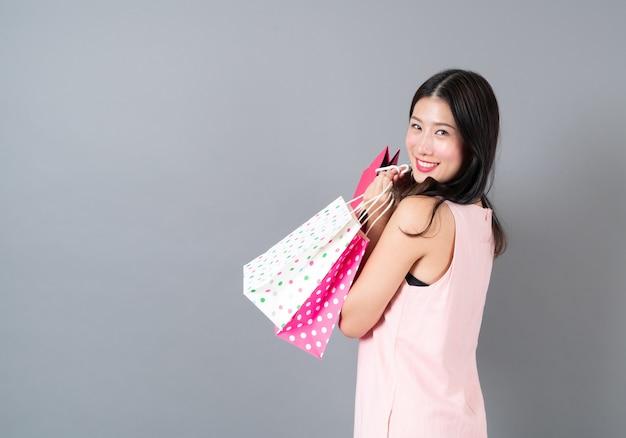 Jovem asiática feliz sorrindo segurando uma sacola de compras em um vestido rosa