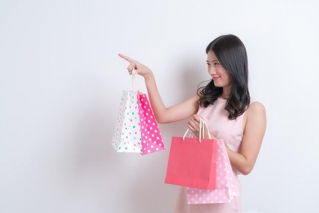 Jovem asiática feliz sorrindo segurando uma sacola de compras