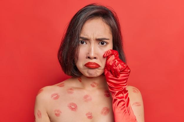 Jovem asiática frustrada e infeliz franze os lábios vermelhos, insatisfeita com algo que parece sombrio para a câmera, fica sem camisa dentro de casa contra uma parede vívida