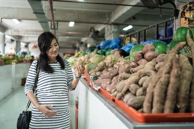 Jovem asiática grávida segurar itens a serem comprados