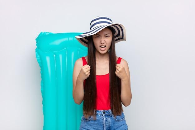 Jovem asiática gritando agressivamente com olhar irritado, frustrado, com raiva e punhos cerrados, sentindo-se furioso. conceito de verão