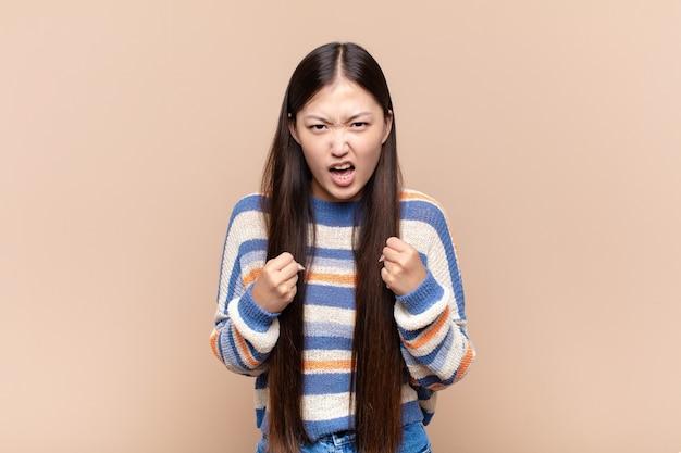 Jovem asiática gritando agressivamente com olhar irritado, frustrado e irritado e punhos cerrados, sentindo-se furiosa