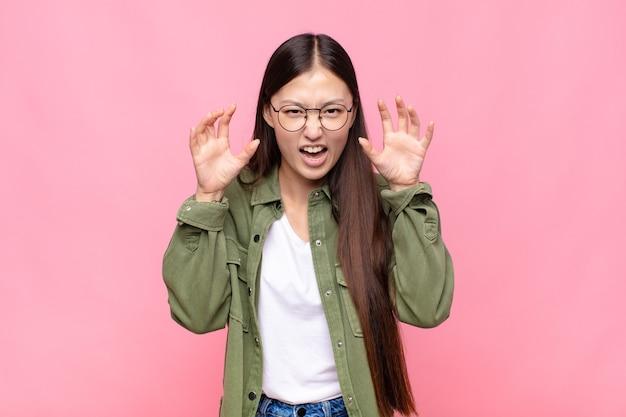 Jovem asiática gritando em pânico ou raiva, chocada, apavorada ou furiosa, com as mãos perto da cabeça