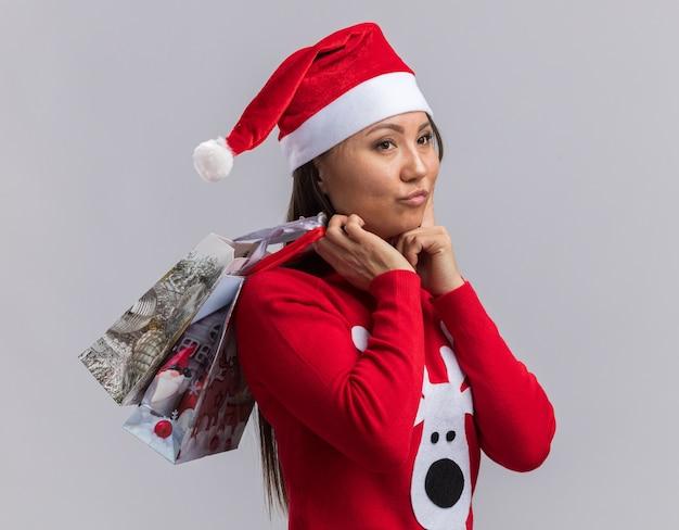 Jovem asiática impressionada com chapéu de natal e suéter segurando uma sacola de presente no ombro e colocando o dedo na bochecha isolado no fundo branco
