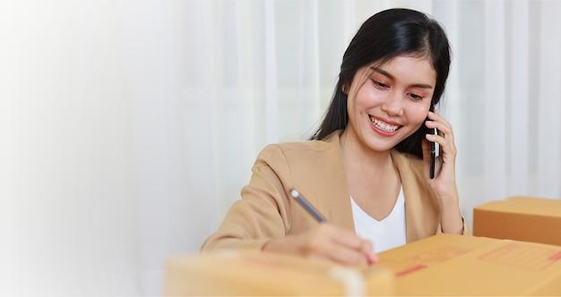 Jovem asiática inteligente e feliz mulher de negócios em vestido casual, trabalhando em casa com um laptop e smartphone com pedido de compra online e embalagem de caixa na mesa (novo conceito normal)