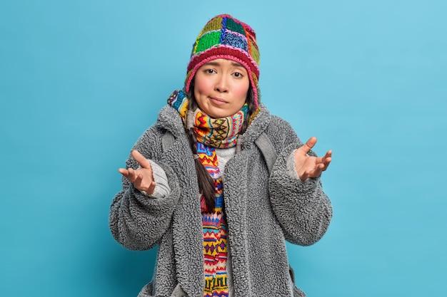 Jovem asiática intrigada e hesitante espalha as palmas das mãos com uma expressão confusa, sem saber o que fazer durante o dia frio de inverno, usa um chapéu de malha, casaco cinza e poses de casaco de pele contra a parede azul