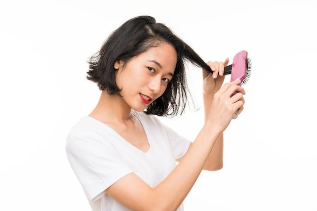 Jovem asiática isolada sobre com pente de cabelo