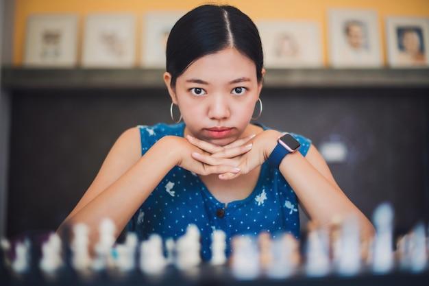 Jovem asiática jogando xadrez em casa