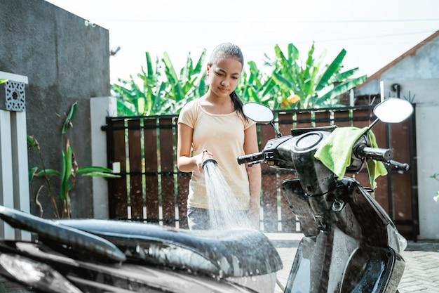 Jovem asiática lavando uma motocicleta