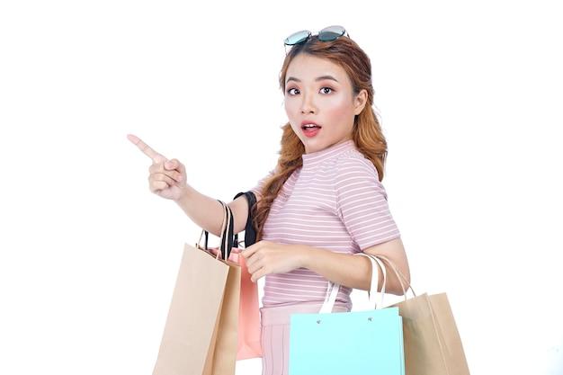 Jovem asiática linda e atraente com sacolas de compras