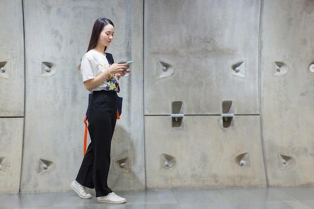 Jovem asiática linda mulher com cabelo comprido segura o smartphone na mão e anda