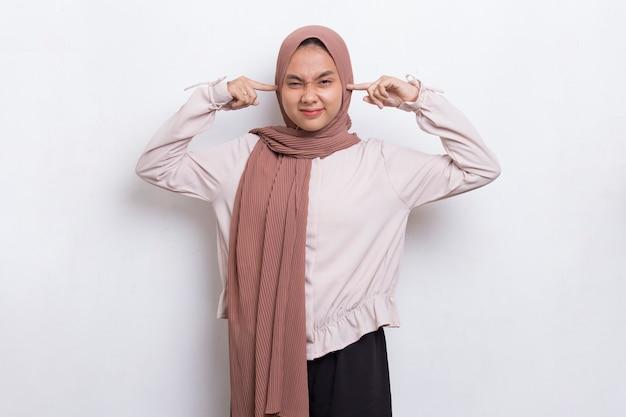 Jovem asiática linda mulher muçulmana cobrindo ambas as orelhas com as mãos isoladas no fundo branco