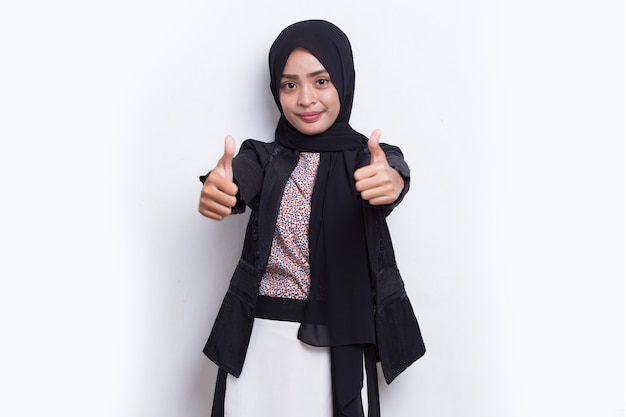 Jovem asiática linda mulher muçulmana com sinal de ok tumb up isolado no fundo branco