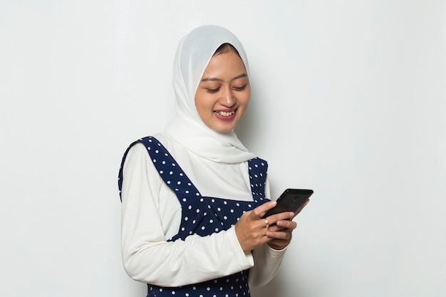 Jovem asiática linda mulher muçulmana usando telefone celular