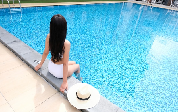 Jovem asiática linda mulher relaxante na piscina.