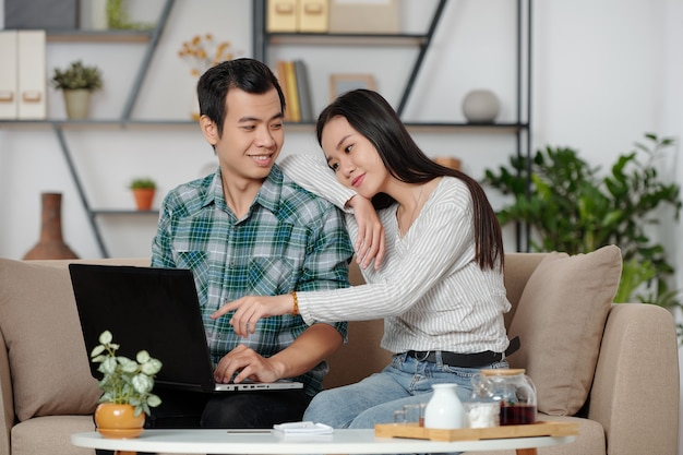 Jovem asiática muito sorridente, apoiada no ombro do namorado e apontando para a tela do laptop, pedindo a ele para comprar algo online para ela