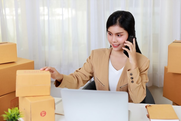Jovem asiática, mulher de negócios inteligente e feliz em vestido casual, trabalhando em casa com um laptop e smartphone
