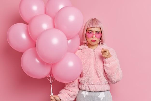 Jovem asiática ofendida com raiva aponta o cabelo rosa para você e culpa alguém em um feriado estragado
