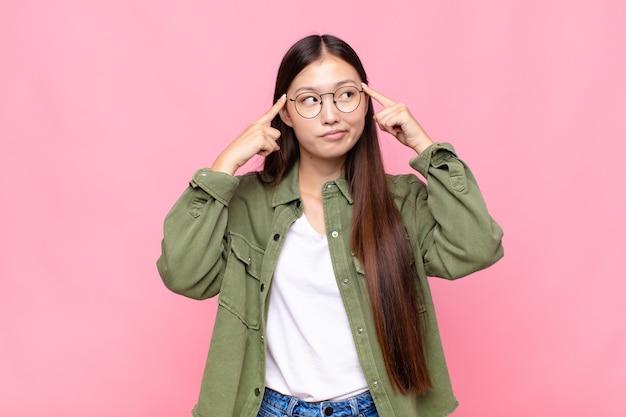 Jovem asiática parecendo concentrada e pensando seriamente em uma ideia, imaginando uma solução para um desafio ou problema