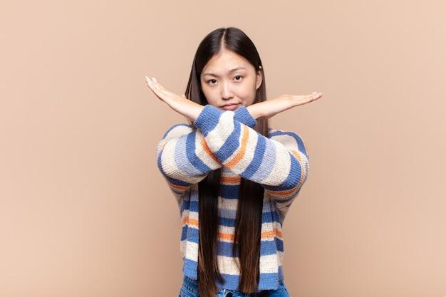 Jovem asiática parecendo irritada e cansada de sua atitude, dizendo o suficiente! mãos cruzadas na frente, dizendo para você parar