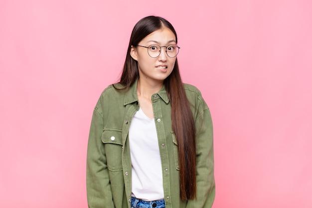 Jovem asiática parecendo perplexa e confusa, mordendo o lábio com um gesto nervoso, sem saber a resposta para o problema