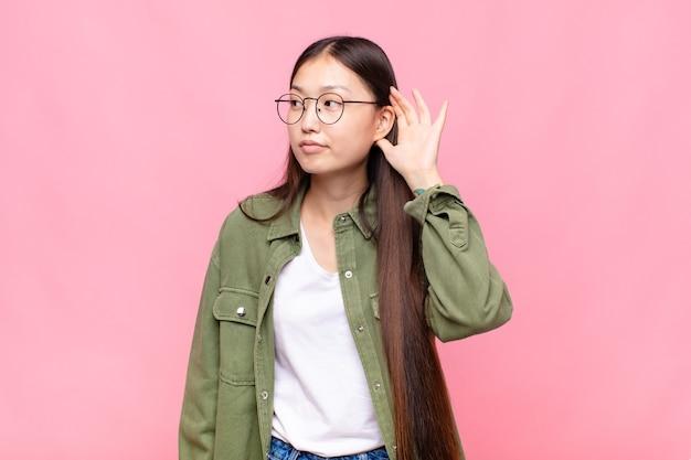 Jovem asiática parecendo séria e curiosa, ouvindo, tentando ouvir uma conversa secreta ou fofoca