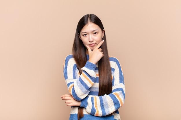 Jovem asiática parecendo séria, pensativa e desconfiada, com um braço cruzado e a mão no queixo, opções de peso