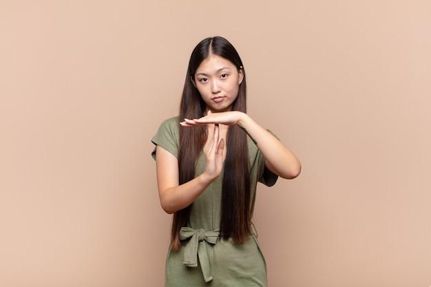 Jovem asiática parecendo séria, severa, zangada e descontente, fazendo sinal de castigo