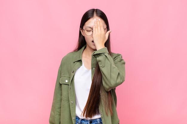 Jovem asiática parecendo sonolenta, entediada e bocejando, com dor de cabeça e uma mão cobrindo metade do rosto