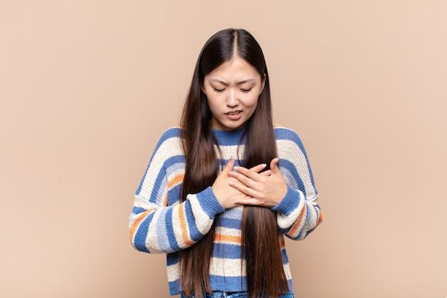 Jovem asiática parecendo triste, magoada e com o coração partido, segurando as duas mãos perto do coração, chorando e se sentindo deprimida