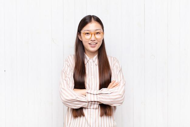 Jovem asiática parecendo uma empreendedora feliz, orgulhosa e satisfeita, sorrindo com os braços cruzados