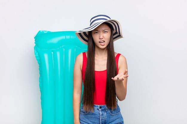 Jovem asiática parecendo zangada, irritada e frustrada gritando