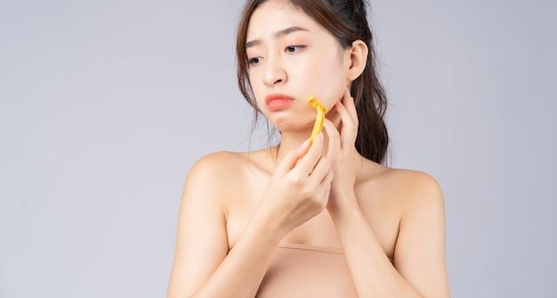 Jovem asiática preocupada com os pelos faciais