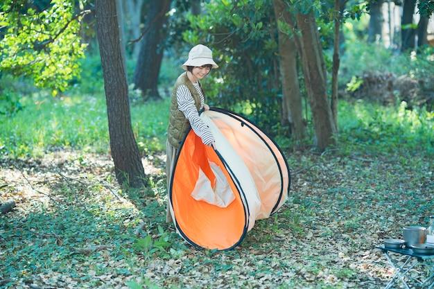Jovem asiática preparando uma barraca para acampar