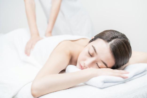 Jovem asiática recebendo massagem em um salão de estética