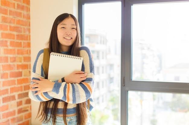 Jovem asiática rindo alegremente com os braços cruzados, numa pose relaxada, positiva e satisfeita
