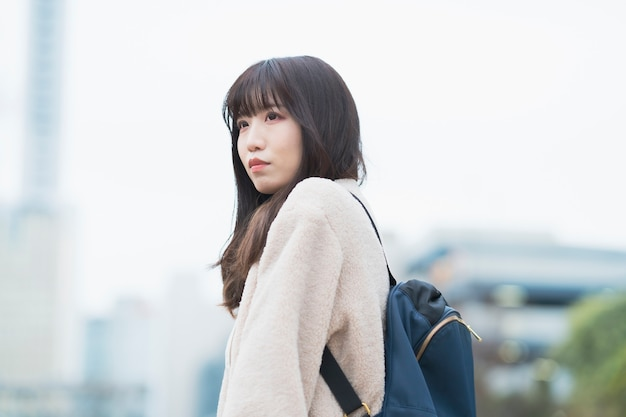 Jovem asiática saindo com uma mochila nas costas