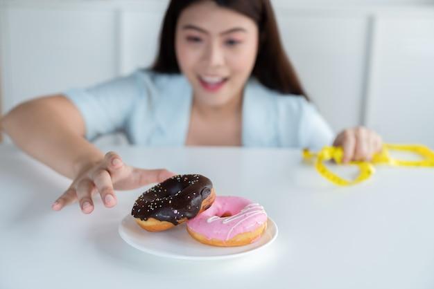 Jovem asiática se estende para comer rosquinhas enquanto faz uma dieta
