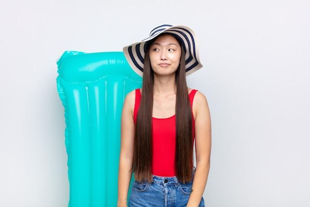 Jovem asiática se perguntando, tendo pensamentos felizes e ideias isoladas