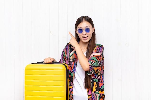Jovem asiática se sentindo alegre e surpresa, sorrindo com uma expressão chocada e apontando para o lado. conceito de férias
