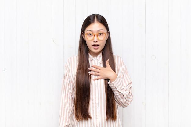 Jovem asiática se sentindo chocada, atônita e surpresa, com a mão no peito e a boca aberta, dizendo quem, eu?
