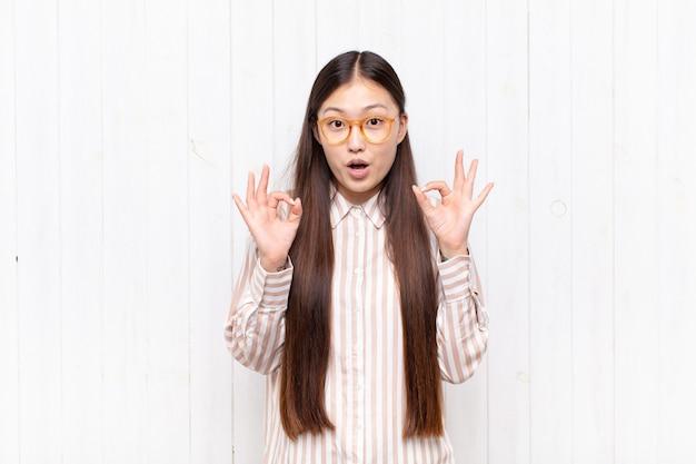Jovem asiática se sentindo chocada, espantada e surpresa, mostrando aprovação e fazendo sinal de ok