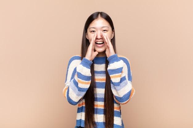 Jovem asiática se sentindo feliz, animada e positiva, dando um grande grito com as mãos perto da boca, gritando