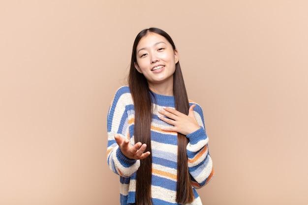Jovem asiática se sentindo feliz e apaixonada, sorrindo com uma mão perto do coração e a outra esticada na frente