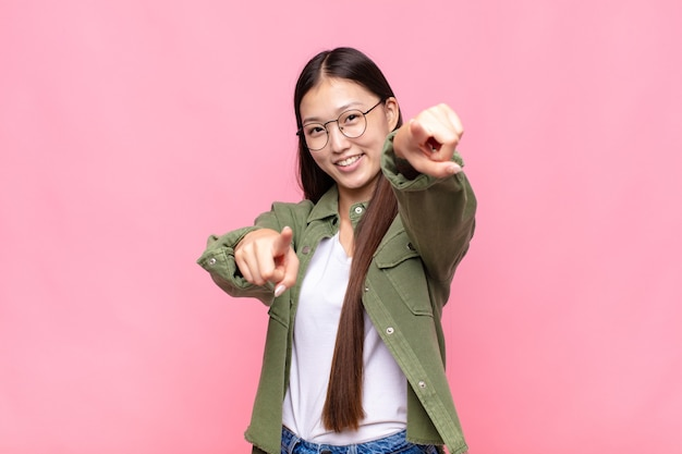 Jovem asiática se sentindo feliz e confiante, apontando com as duas mãos isoladas