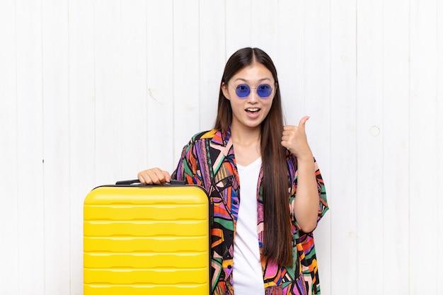 Jovem asiática se sentindo feliz, maravilhada, satisfeita e surpresa, mostrando gestos de ok e polegar para cima, sorrindo