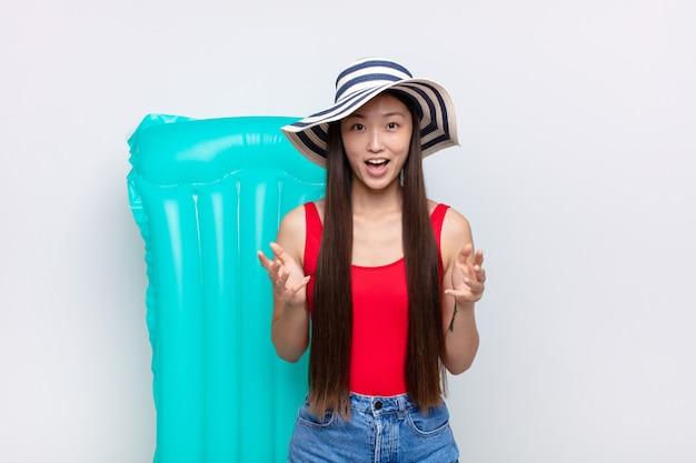 Jovem asiática se sentindo feliz, surpresa, sortuda e surpresa, gosta de dizer omg sério? inacreditável. conceito de verão