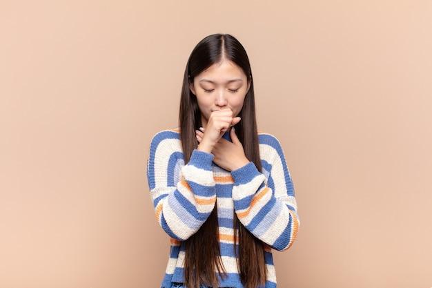 Jovem asiática se sentindo mal com dor de garganta e sintomas de gripe, tosse com a boca coberta
